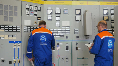 engineers stand at network power cabinets controlling readings Footage