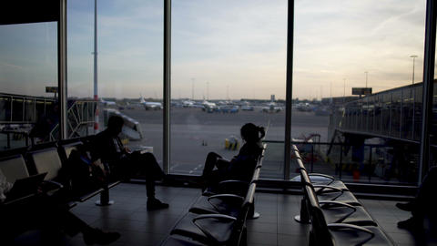 Male and female passengers sitting at departure lounge, waiting for plane Footage