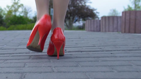 Feet of lady walking street in red high heel shoes alone, risk of attack, danger Footage