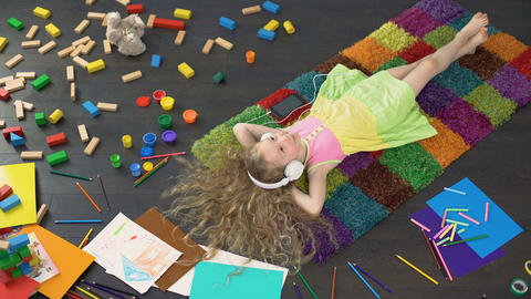 Cheerful child lying on colorful carpet and listening to music in headphones Footage