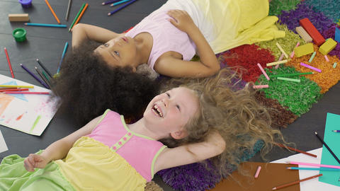 Best friends lying on colorful carpet and laughing, enjoying cool holidays Footage