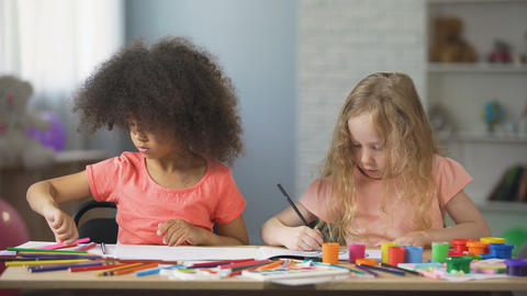Early education, two multi-ethnic female kids drawing with colorful pencils Footage