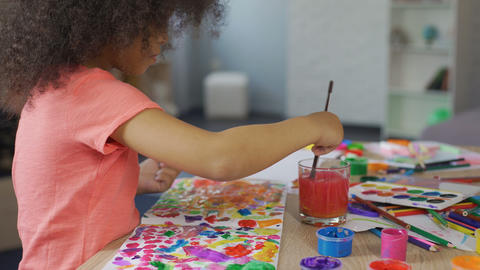Little Afro-American girl practicing painting at kindergarten, leisure activity Footage