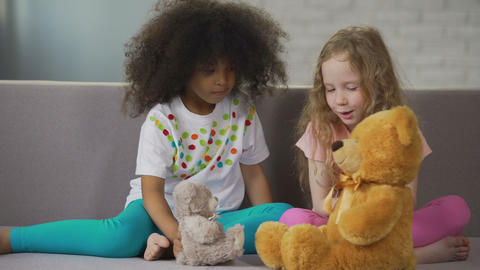 Two little multiracial girls sitting on couch and playing with teddy bears Footage