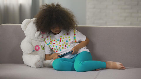Little African American girl sitting on couch and playing game on cellphone Footage