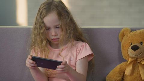 Cute female kid enjoying game on smartphone, gadget addiction, childhood ライブ動画