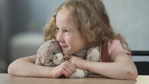 Happy child sitting at the table, holding teddy bear and smiling. Childhood Footage