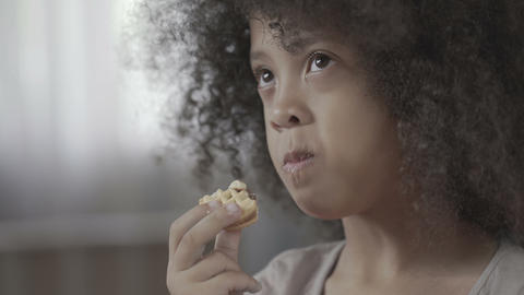 Little black-haired child chewing tasty cookie with appetite, unhealthy food Live Action