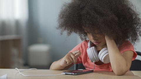 African American girl sitting alone and watching movie on smartphone, gadget Live Action