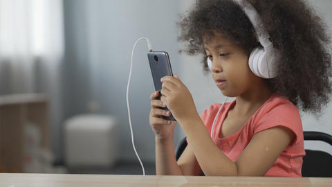 Pretty Afro-American child wearing earphones and listening to music on cellphone Footage