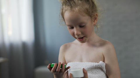Pretty female kid opening cream tube and preparing for daily beauty procedures Footage