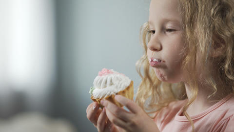 Close-up of pretty little girl biting cake and enjoying perfect taste of dessert Footage