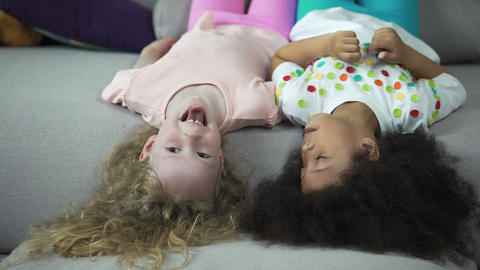 Happy multiracial kids lying on couch and having fun, childhood and holidays Footage