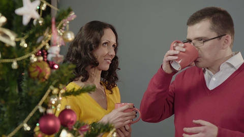 Man and woman having nice conversation over cup of hot beverage, New Year party Live Action