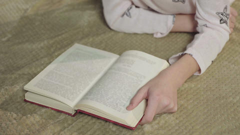 Little girl reading interesting book about adventures, happy childhood, dreams Footage