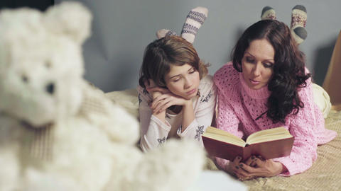 Mom and daughter comfortably lying in bed, reading fairy tales and dreaming Live Action