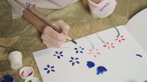 Girl drawing glade with colorful flowers with gouache, painting her mood, art Footage