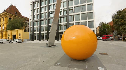 Round orange sculpture standing near Music Academy in Zagreb, modern art Footage