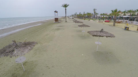 Aerial shot along coastline with straw parasols and palms, tourism and relax Footage