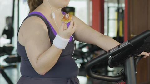Obese young woman with weak willpower eating donut during workout at gym Live Action
