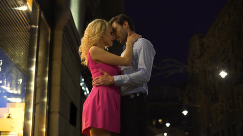 Blonde lady gently hugging her beloved man, romantic date in night city center Live Action