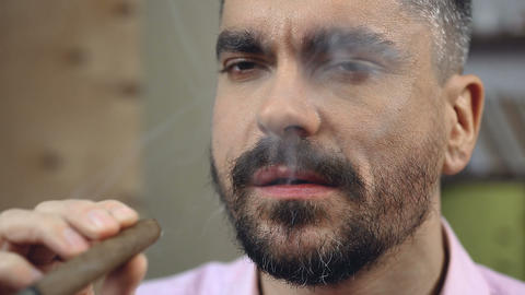 Bearded man trying new flavor of Cuban cigars, smoking habit, masculinity Live Action