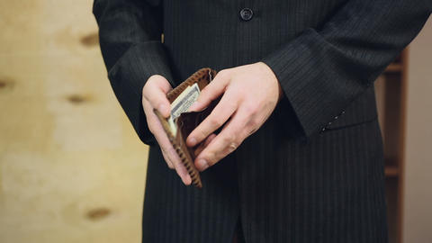 Respectable businessman in expensive suit counting money in wallet before date Live Action