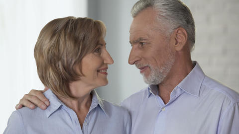 Happy elderly couple looking at each other and smiling at camera, advertising Footage