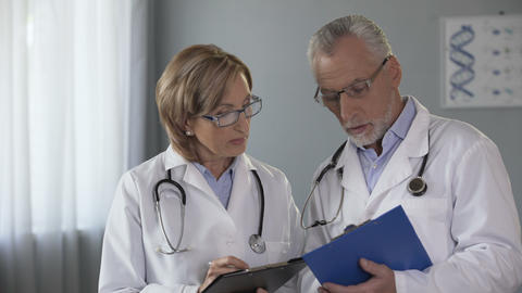 Experienced male and female doctors comparing results, consulting on diagnosis Footage