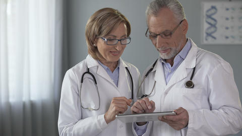 Female and male physicians looking at tablet with admiration, app for medics Footage