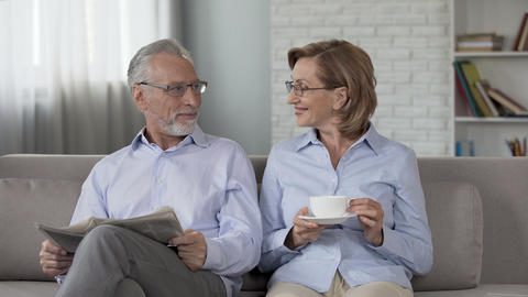 Aged couple sitting on couch, man reading newspaper, woman enjoying tea, advert Footage