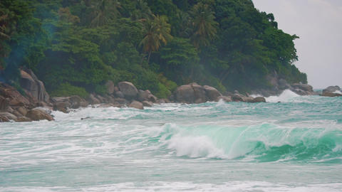 sea waves break against the rocks on a tropical island. Slow motion Footage