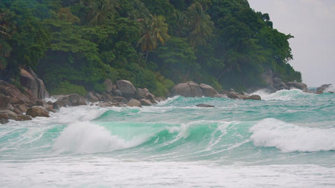 waves scatter around the rocks on the island, slow motion Footage