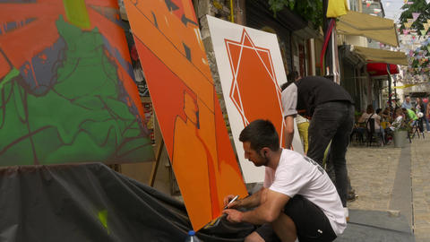Street artists paiting on canvas outside during open air arts festival Footage