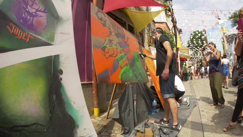 Graffiti artists painting on canvas exterior Footage