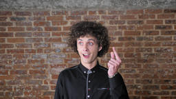 Young man with curly hair coming up with idea or solution, pointing finger up Footage
