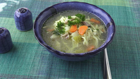 Chicken noodle soup - broth. Traditional chicken soup served in a bowl Live Action