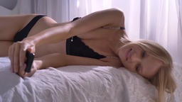 Young sexy blonda woman is laying in lingerie on bed and watching photos on ビデオ