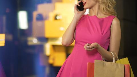 Glamorous girl enjoying expensive shopping, talking over phone, fashion boutique Footage