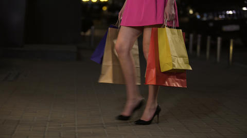 Girl with full shopping bags looking at shop windows with pleasure, shopaholic Live Action