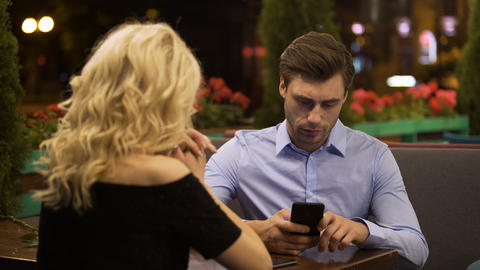 Businessman not paying attention to his talkative girlfriend, addicted to gadget Live Action