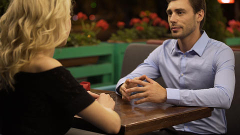Young loving couple sitting in cozy restaurant enjoying each other's company Footage