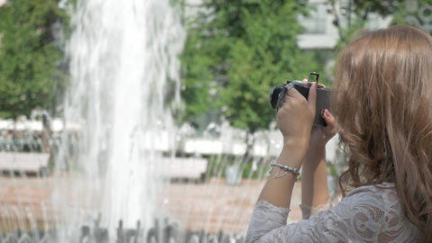 Beautiful girl is taking photos of a city fountain, on a vintage camera GIF