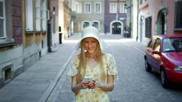 Woman texting on street. Cheerful woman in white hat walking on old town street Footage
