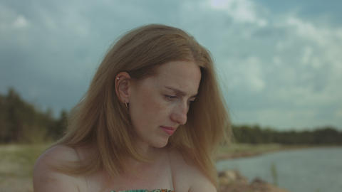 Portrait of pensive ginger woman resting at seaside GIF