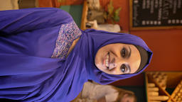 Vertical video shot, portrait of young muslim woman in hijab smiling at camera Footage