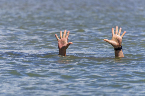 pair of masculine hands sticks out of the sea water Fotografía