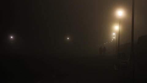 Couple walking in a foggy night in the park Footage
