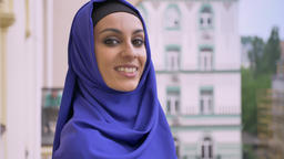 Young charming muslim woman in hijab looking at camera and smiling, standing in ビデオ