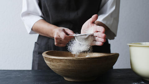 Female hands sifting flour by bowl Footage